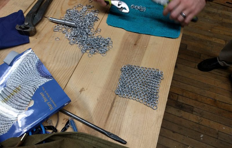 Chain Mail sits on the NESIT workbench while Andrew works on connecting new pieces